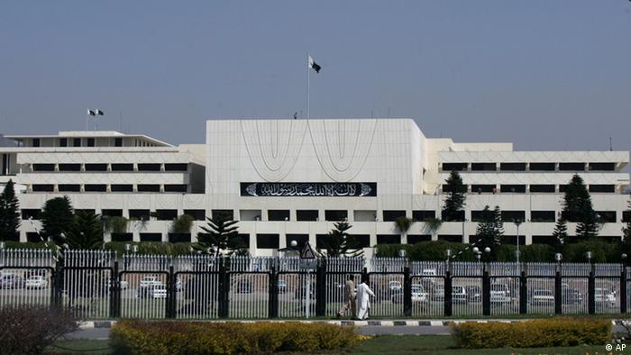 Pakistani men walk past Parliament House building