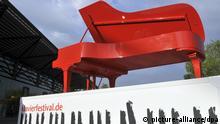 Ein roter Flügel, das Markenzeichen des Klavier-Festivals Ruhr 2009, wirbt am Freitag (08.05.2009) vor der Jahrhunderthalle in Bochum. Zu dem Festival in Konzertsälen und umgebauten Fabrikhallen des Ruhrgebietes werden bis zum 17. Juli wieder um die 60 000 Besucher erwartet. 77 Konzerte stehen auf dem Programm. Das komplett privatfinanzierte Festival gilt als eines der renommiertesten weltweit undlegt besonderen Wert auf die Förderung des Nachwuchses. Foto: Bernd Thissen +++(c) dpa - Report+++