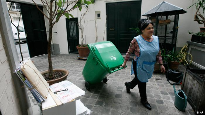 Portugal's Eugenia Manuel brings back a garbage bin in the courtyard of the apartment building where she works as a concierge, or guardian, in Paris, Wednesday March 26, 2008. They take out the garbage, sweep stairwells, keep a trained eye peeled for trespassers and listen to gripes, gossip and, sometimes, heartaches. In the past decade, Paris alone has lost at least 10,000 concierges, or guardians, and France has lost some 100,000, replaced mainly by cleaning companies. (ddp images/AP Photo/Jacques Brinon)