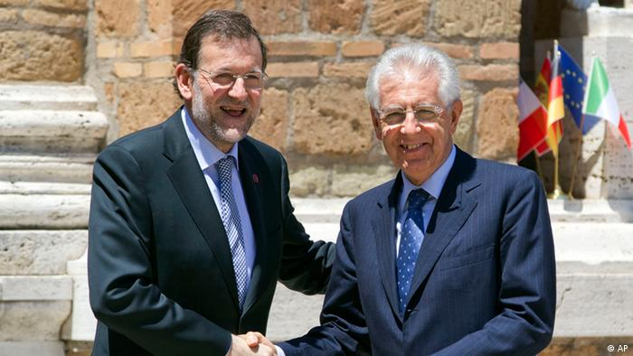 Italian Premier Mario Monti, right, greets Spanish Mariano Rajoy as she arrives for a meeting in Rome