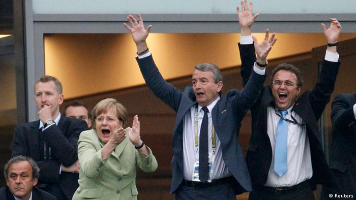 (L-R) UEFA President Michel Platini, German Chancellor Angela Merkel, president of the German soccer federation (DFB) Wolfgang Niersbach and German Interior Minister Hans-Peter Friedrich react after a goal that was disallowed during the quarter-final soccer match between Germany and Greece at the PGE Arena in Gdansk, June 22, 2012. REUTERS/Peter Andrews (POLAND - Tags: SPORT SOCCER POLITICS)