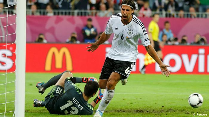 Greece's goalkeeper Michalis Sifakis (L) lies on the ground as Germany's Sami Khedira celebrates his goal during their Euro 2012 quarter-final soccer match at the PGE Arena in Gdansk, June 22, 2012. REUTERS/Thomas Bohlen (POLAND - Tags: SPORT SOCCER)