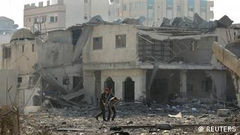 Hamas' security members walk through the wreckage of a building in Gaza City