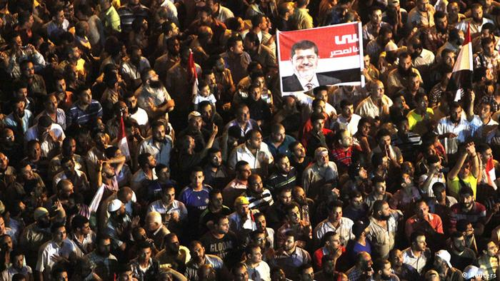Supporters of Muslim Brotherhood's presidential candidate Mohamed Morsy hold up a poster of Morsy during a demonstration against the delay of the Egyptian presidential results and against the Supreme Council for the Armed Forces (SCAF) at Tahrir square in Cairo June 22, 2012. Egypt's military rulers dismissed complaints from protesters on Friday that it was entrenching its rule and blamed Morsy for stirring up emotions that drew thousands onto Cairo's Tahrir Square. Morsy shot back that the generals were defying the democratic will of the people and said protests would go on. But he stopped short of repeating a claim to have won last weekend's election, urging simply a rapid announcement of the result, and praised the army as patriotic. REUTERS/Asmaa Waguih (EGYPT - Tags: POLITICS ELECTIONS)