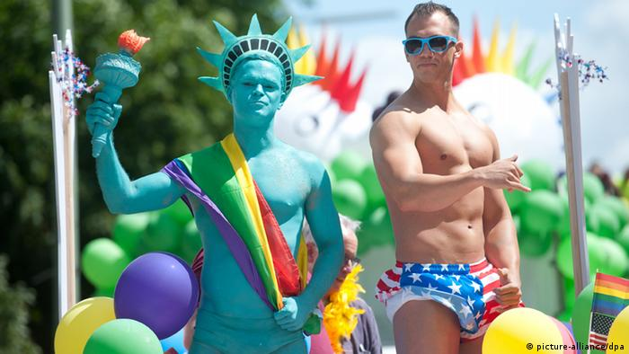 A man dressed as the Statue of Liberty and another wearing a US flag as shorts atop a float