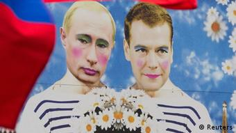 Russian gay-rights activists fly their national flag next to a poster with a caricature painting of Russian President Vladimir Putin and Prime Minister Dmitry Medvedev during the Christopher Street Day (CSD) parade in Berlin, June 23, 2012.