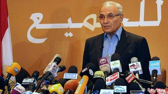 Former prime minister and current presidential candidate Ahmed Shafik listens to the Egyptian national anthem before a news conference in Cairo June 21, 2012.