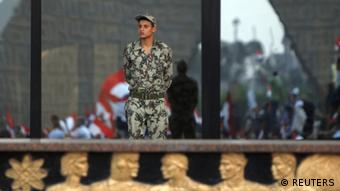 An army soldier looks on as supporters of former prime minister and current presidential candidate Ahmed Shafik shout slogans against the Muslim Brotherhood's presidential candidate