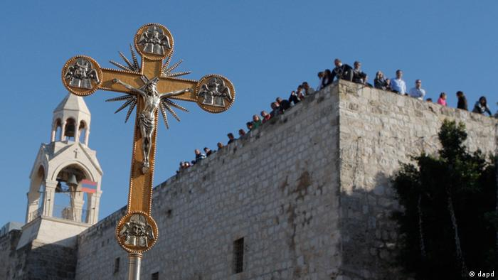 In this Friday, Dec. 24, 2010 file photo, a cross is seen backdropped by the Church of Nativity, traditionally believed by Christians to be the birthplace of Jesus Christ, during a Christmas parade in the West Bank town of Bethlehem. A long-needed renovation of the Church of the Nativity is slowly getting under way in Bethlehem, the town of Jesus' birth, in the face of political and religious conflicts that have kept one of Christendom's holiest sites in a state of decay for centuries. (AP Photo/Nasser Shiyoukhi, File).