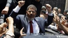 Presidential candidate Mohamed Morsy of the Muslim Brotherhood waves to his supporters after casting his vote at a polling station in a school in Al-Sharqya, 60 km (37 miles) northeast of Cairo in this June 16, 2012 file photo. Islamist Mohamed Morsy of the Muslim Brotherhood was elected president of Egypt after he defeated former general Ahmed Shafik in last weekend's run-off vote, the state election committee said on June 24, 2012. REUTERS/Ahmed Jadallah/Files (EGYPT - Tags: POLITICS ELECTIONS)