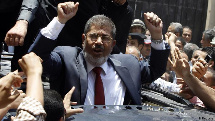 Presidential candidate Mohamed Morsi of the Muslim Brotherhood waves to his supporters after casting his vote at a polling station in a school in Al-Sharqya, 60 km (37 miles) northeast of Cairo in this June 16, 2012 file photo