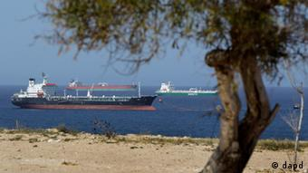 Ships are at anchors in the Mediterranean sea next to the Zawiya Oil Refinery in Zawiya