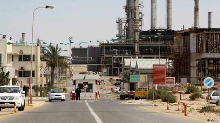 A security guard stands at at a gate inside the Zawiya Oil Refinery