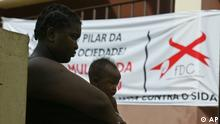 An unidentified mother and child wait outside a polling station in Maputo, Wednesday, Dec. 1, 2004. Mozambique is holding it's third presidential and parliamentary elections with some polling stations hanging up banners with red ribbons in commemoration of World Aids Day. (AP Photo)