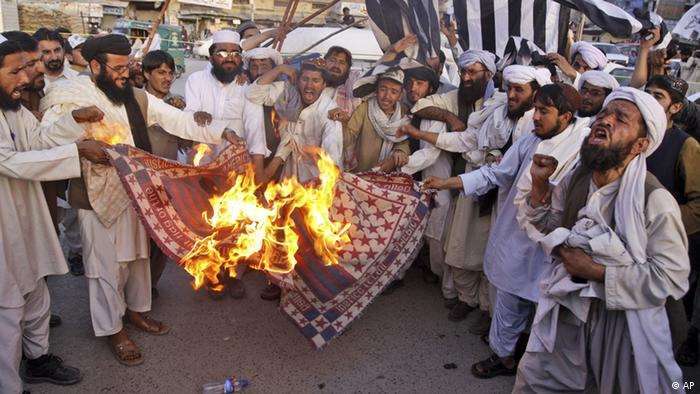 Supporters of Pakistan Defense Council, a coalition of Islamic parties, burn a representation of a US flag