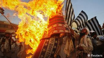 Supporters of the Defense of Pakistan Council burn an American flag during a rally in Quetta