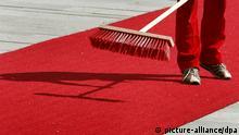 Roter Teppich Besen kehren Symbolbild