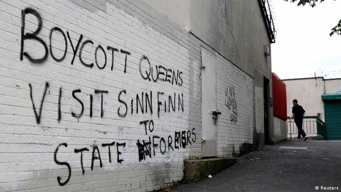 A man walks past graffitti painted on a wall in a nationalist area of north Belfast during Britain's Queen Elizabeth's two day tour of Northern Ireland, June 26, 2012.REUTERS/Cathal McNaughton (BRITAIN - Tags: ROYALS ENTERTAINMENT)