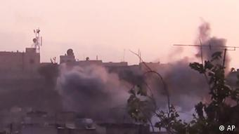 In this image made from amateur video released by the Shaam News Network and accessed Tuesday, June 26, 2012, smoke rises from buildings following purported shelling in Homs, Syria. (Foto:Shaam News Network via AP video/AP/dapd) TV OUT, THE ASSOCIATED PRESS CANNOT INDEPENDENTLY VERIFY THE CONTENT, DATE, LOCATION OR AUTHENTICITY OF THIS MATERIAL