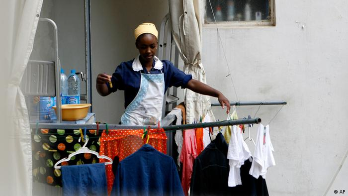 An Ethiopian maid hangs washed clothes as she stands on a balcony in Beirut, Lebanon Photo: AP Photo/Grace Kassab