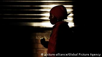 A women wearing an apron and head covering in the shadows (Photo:Luca Ghidoni)