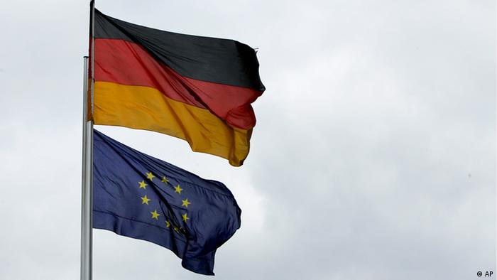 A German and EU flag wave on flagpoles next to each other