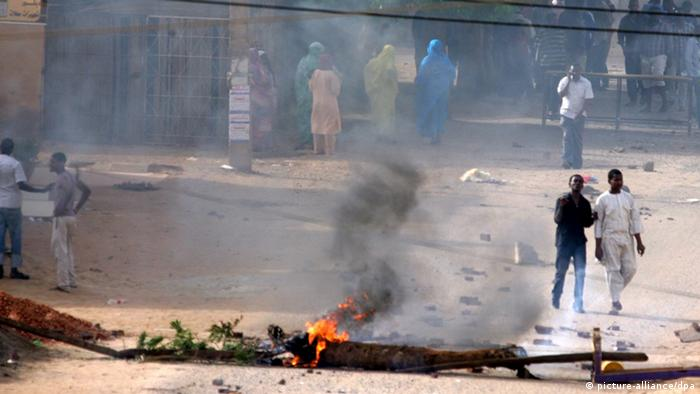 People standing near burning debris after protests in Khartoum