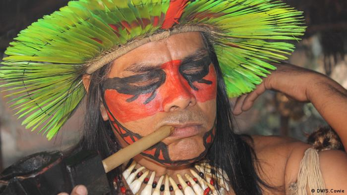 A member of the Indian museum community in traditional decoration, smoking a pipe.