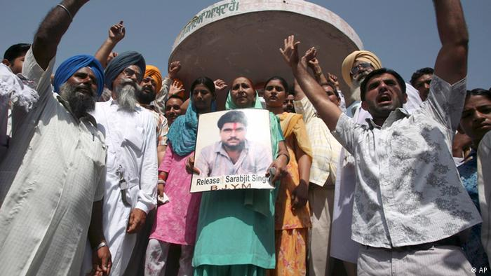 Dalbir Singh, center, sister of Sarabjit Singh, an Indian prisoner who is facing execution in Pakistan, holds a portrait of Singh, during a protest pressing for his release, in Bikhiwind, some 45 kilometers (28 miles) from Amritsar, India, Thursday, June 25, 2009 (Photo: AP Photo/Altaf Qadri)