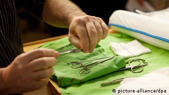 Surgical instruments for a Jewish circumcision ceremony being laid out on a green cloth