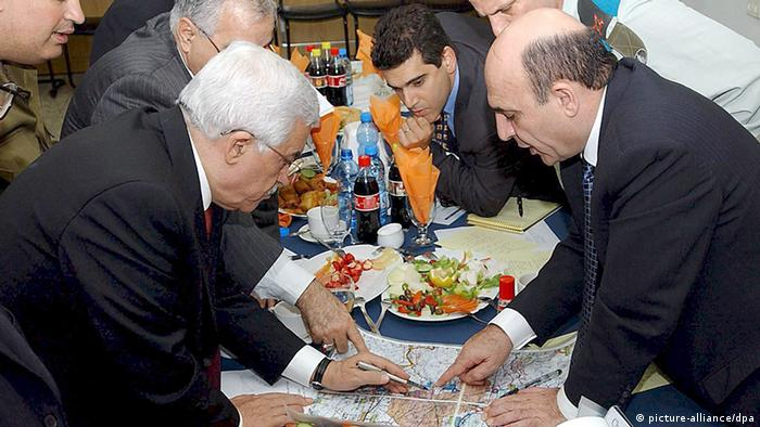 A photograph supplied by the Palestinian Authority shows Palestinian President Mahmoud Abbas (Abu Mazen), left, reviewing maps of what appears to be East Jerusalem with Israeli Defense Minister Shaul Mofaz as unidentified military aides look on during a meeting held on Tuesday evening, 8 March 2005 in the Erez Checkpoint crossing area between Israel and the Gaza Strip. In the meeting it was decided that Israel would turn over security in two West Bank towns, Jericho and Tulkarm, to the Palestinian Authority, but a firm timetable was not agreed on. EPA/OMAR RASHIDI-PALESTINIAN AUTHORITY +++(c) dpa - Bildfunk+++