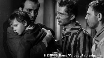 """Filmfoto """"Nackt unter Wölfen"""" - Ein Mann hält einen kleinen Jungen im Arm, zwei weitere stehen daneben"""