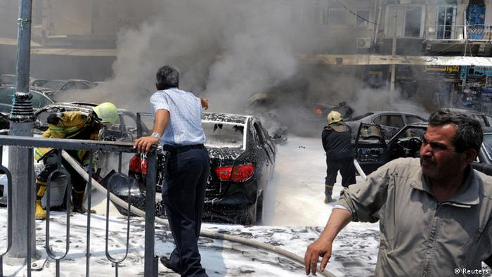 Civil Defence members extinguish fires on cars at the site of an explosion outside Syria's highest court in central Damascus on Thursday. REUTERS/SANA/Handout
