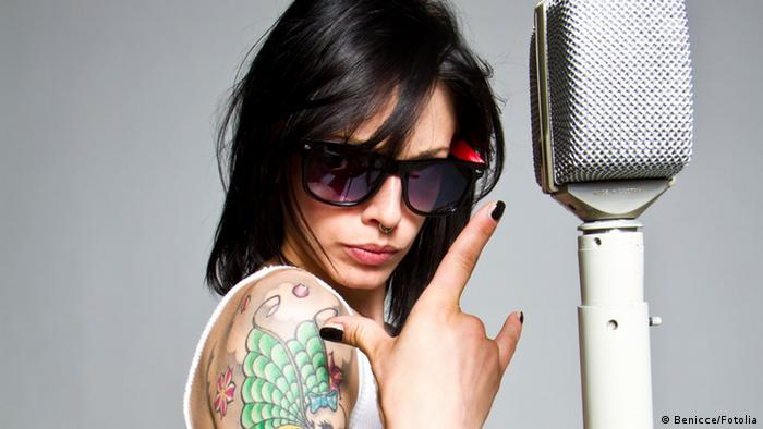 Woman with sunglasses, tattoo and microphone (Benicce/Fotolia)