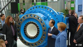 Засновник компанії Йоахім Фурлендер (л.) приймає на виставковому стенді канцлера Анґелу Меркель. Архівне фото