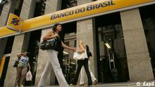 People walk by a Banco do Brasil bank in Rio de Janeiro, Friday, Jan. 9, 2009. Brazil's leading state-owned bank said Friday it will pay 4.2 billion reals ($1.8 billion) for a stake in the banking unit of one of the nation's biggest conglomerates to help ease credit in Latin America's largest economy. Banco do Brasil SA said in a statement to regulators that the deal, when completed, will give it a 50 percent share in Votorantim Finances SA. (ddp images/AP Photo/Ricardo Moraes)