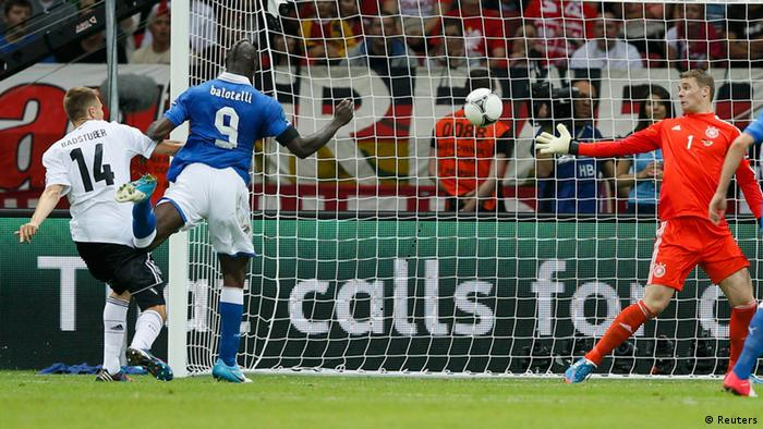 Italy's Mario Balotelli (2L) scores a goal against Germany's Manuel Neuer during their Euro 2012 semi-final soccer match at the National Stadium in Warsaw, June 28, 2012. REUTERS/Pascal Lauener (POLAND - Tags: SPORT SOCCER TPX IMAGES OF THE DAY)