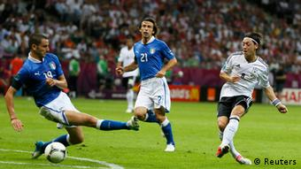 Germany's Mesut Oezil (R) makes a pass past Italy's Leonardo Bonucci (L) and Andrea Pirlo during their Euro 2012 semi-final soccer match at the National Stadium in Warsaw, June 28, 2012.