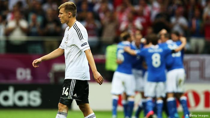 WARSAW, POLAND - JUNE 28: Holger Badstuber of Germany shows his dejection as Italy plaayers celebrate scoring the opening goal during the UEFA EURO 2012 semi final match between Germany and Italy at National Stadium on June 28, 2012 in Warsaw, Poland. (Photo by Alex Grimm/Getty Images)