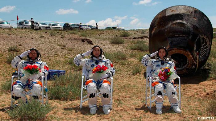 Chinese astronauts Jing Haipeng (C), Liu Wang (L) and Liu Yang, China's first female astronaut, salute in front of the re-entry capsule of China's Shenzhou 9 spacecraft in Siziwang Banner, Inner Mongolia Autonomous Region June 29, 2012. China's Shenzhou 9 spacecraft returned to Earth on Friday, ending a mission that put the country's first woman in space and completed a manned docking test critical to its goal of building a space station by 2020. REUTERS/Xinhua/Ren Junchuan (CHINA - Tags: MILITARY SCIENCE TECHNOLOGY) NO SALES. NO ARCHIVES. FOR EDITORIAL USE ONLY. NOT FOR SALE FOR MARKETING OR ADVERTISING CAMPAIGNS. THIS IMAGE HAS BEEN SUPPLIED BY A THIRD PARTY. IT IS DISTRIBUTED, EXACTLY AS RECEIVED BY REUTERS, AS A SERVICE TO CLIENTS. CHINA OUT. NO COMMERCIAL OR EDITORIAL SALES IN CHINA. YES