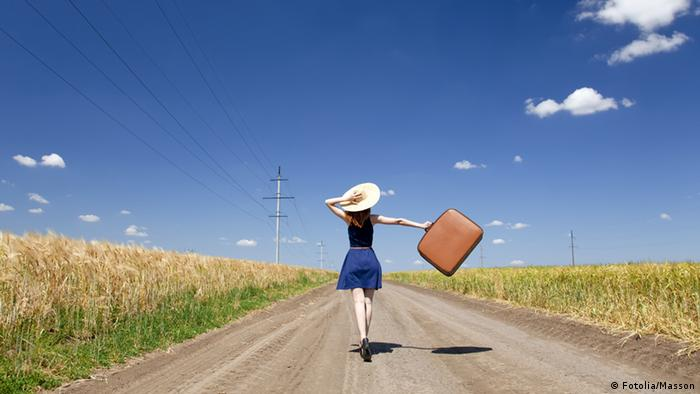 Lonely girl with suitcase at country road. Fotolia #33389308