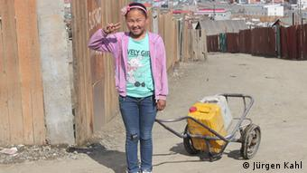 A young girl fetches water in the yurt slum of Ulan Bator
