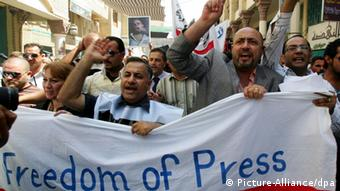 Bild 1: Iraqi journalists shout slogans and carry banners during a rally in Al-Mutanabi Street in Baghdad, Iraq on 14 August 2009. The journalists protest over what they say are dangerous threats by a top Shiite political leader in a war of words over a deadly bank heist in the capital. Jalal Eddin Saghir, a leader of the formerly Iran-based Supreme Iraqi Islamic Council, is accused of making violent threats against journalist Ahmad Abdel Hussein during a Friday sermon over an article in the state-run Al-Sabah newspaper alleging SIIC links to the 28 July raid in central Baghdad, in which eight guards were killed and 3.8 million dollars were stolen. EPA/ALI ABBAS +++(c) dpa - Report+++
