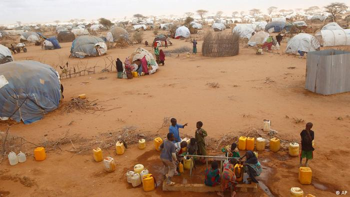 In this photo taken Sunday, Aug. 7, 2011, Somali refugees collect water at the Ifo refugee camp outside Dadaab, eastern Kenya, 100 kilometers (62 miles) from the Somali border.