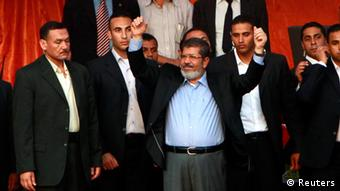 Egypt's Islamist President-elect Mohamed Mursi waves to his supporters while surrounded by his body guards