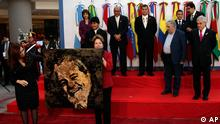 Argentina's President Cristina Fernandez, left, gives to Brazil's President Dilma Rousseff, second from left, a painting of Brazil's former President Luiz Inacio Lula da Silva during a meeting by the Union of South American Nations (UNASUR) in Mendoza, Argentina, Friday, June 29, 2012. (AP Photo/Natacha Pisarenko)