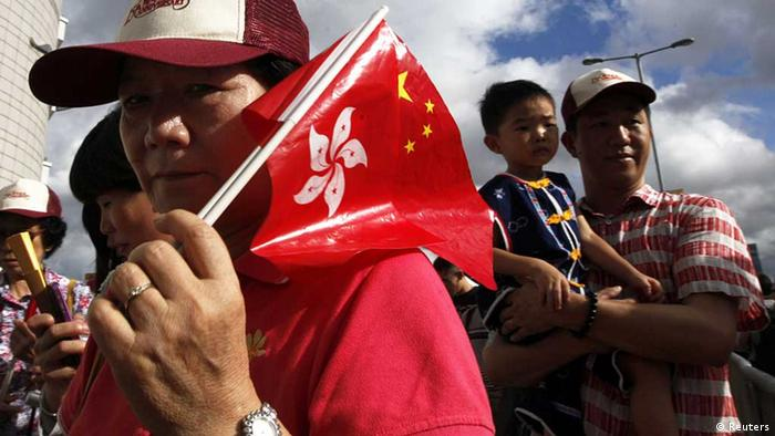 A resident carrying Hong Kong and Chinese flags attends a flag-raising ceremony to mark the 15th anniversary of the territory's handover to Chinese rule, in Hong Kong July 1, 2012. REUTERS/Tyrone Siu (CHINA - Tags: POLITICS ANNIVERSARY) Eingestellt vonn Eleonore Uhlich