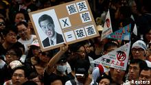 A protester holds a sign mocking new leader Leung Chun-ying during a demonstration urging him to step down in Hong Kong July 1, 2012, during the 15th anniversary of the territory's handover to China. Leung was sworn into office on Sunday by Chinese President Hu Jintao for a five-year term in which he will confront challenges ranging from human rights to democracy after a tumultuous year of transition and protest. REUTERS/Bobby Yip (CHINA - Tags: POLITICS ANNIVERSARY CIVIL UNREST)
