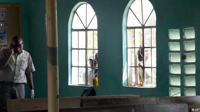 Men look in through the church windows as a member of the Kenyan security forces, left, inspects the scene inside the African Inland Church in Garissa, Kenya