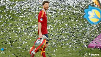 Spain's Xabi Alonso carries the trophy on the pitch after defeating Italy to win the Euro 2012 final soccer match at the Olympic stadium in Kiev, July 1, 2012. REUTERS REUTERS/Charles Platiau (UKRAINE - Tags: SPORT SOCCER TPX IMAGES OF THE DAY)